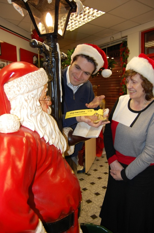 David Russell & Arleen Barton from ABC Estate Agents of Glengormley, present Santa with a Gift Tag he won't want to throw away this Christmas; NI Water's stop valve tags are available free of charge by calling Waterline on 08457 440088.